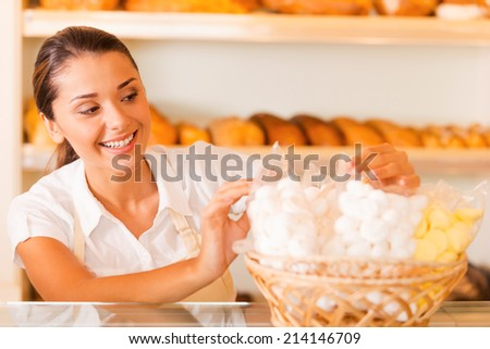 Packing fresh cookies for sale. Beautiful young woman in apron packing cookies and smiling while standing in bakery shop - stock photo