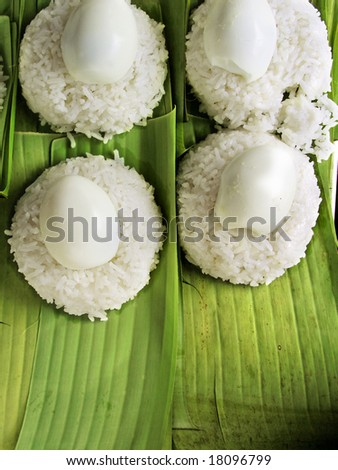 Packing Nasi Lemak with babana leaf topped with eggs