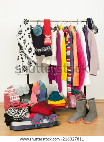 Packing the suitcase for winter vacation. Wardrobe with clothes nicely arranged and a full luggage. Dressing closet with colorful winter clothes and accessories on hangers. - stock photo