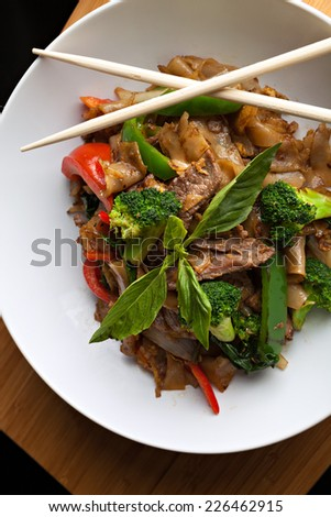 Pad kee mao drunken noodle thai dish with beef and mixed vegetables. - stock photo