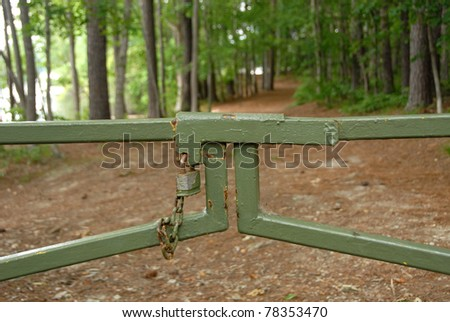 Pad locked gate closing a National park pathway to a nature trail. Signs of hard economic times in the United States. - stock photo