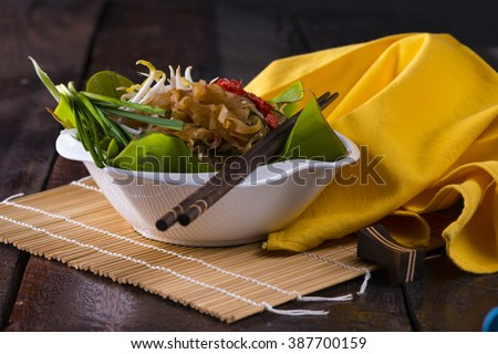 Pad Thai, a Thai speciality with a lot of variation. The dish is in a white bowl a Banana leafs. This dish is sold in the street restaurant and also served in banana leaf - stock photo