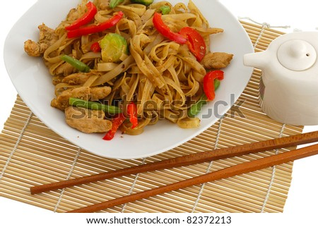 Pad Thai dish on straw pad with chopsticks and soy sauce isolated on white background - stock photo