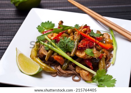 Pad Thai with chicken and buckwheat noodles on white plate with chopsticks - stock photo