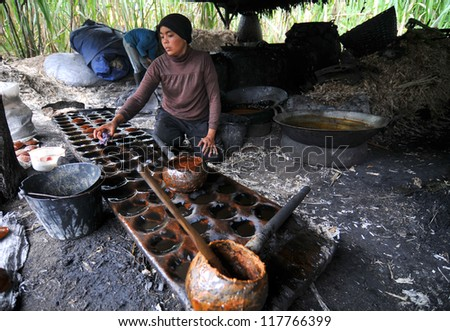 PADANG, INDONESIA - MAR 23 : A woman processing red sugar from sugar cane to be sell at the market on March 23, 2010, Padang, Indonesia