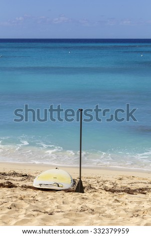 Paddle board and a paddle standing on a sandy beach with amazing turquoise sea in the background. - stock photo