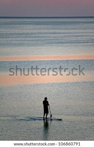 paddle boarder at dusk - stock photo
