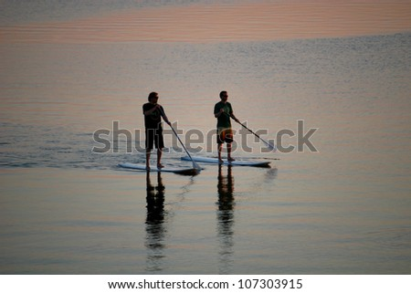 paddle boarders at dusk - stock photo