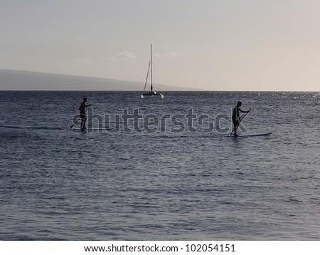 Paddle Boarding across ocean - stock photo