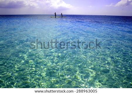 Paddle Boarding along Grand Cayman's 7 Mile Beach - stock photo