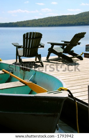 Paddle boat and two adirondack wooden chairs on dock facing a blue lake - stock photo