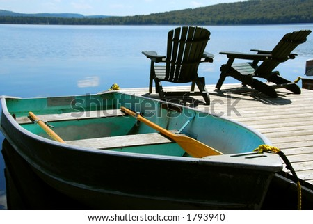 Paddle boat and two adirondack wooden chairs on dock facing a blue lake, shalow DoF. - stock photo