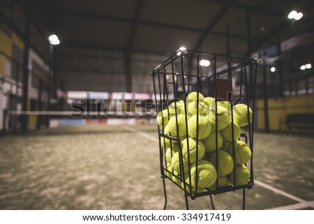 Paddle tennis basket in court with balls.