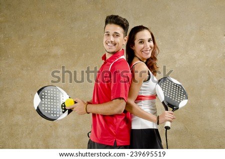 Paddle tennis couple posing on concrete wall court smiling with rackets - stock photo