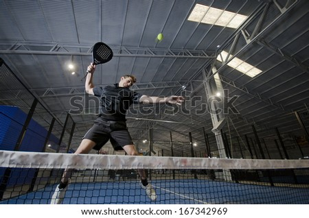 Paddle tennis player  jumping and smashing ball - stock photo