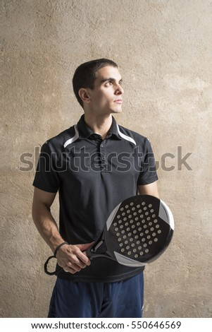 Paddle tennis player posing on wall