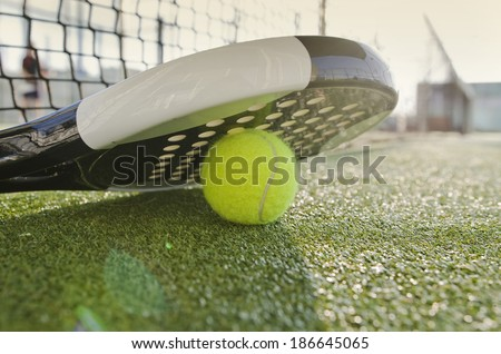 Paddle Tennis racket, ball and net with flare light - stock photo