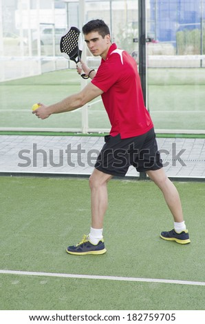 Paddle tennis serve. Young man in outdoors court