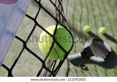 Paddle tennis shot on net, objects like racket and balls in the background, blurred. Action sports image.