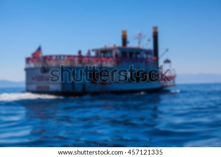 Paddle wheel boat on lake with blur applied to image.