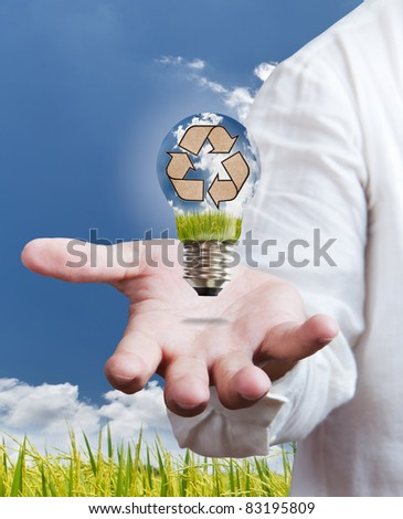 paddle , windmill and blue sky in light bulb on hand - stock photo