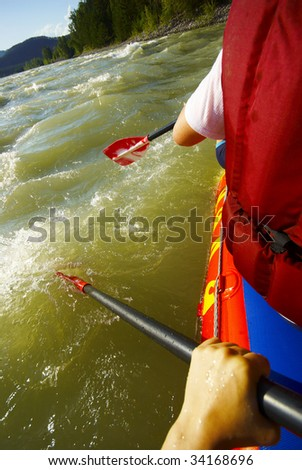 paddling on a raft, shot from the raft - stock photo