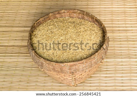 paddy rice in bamboo basket on mat weave background - stock photo
