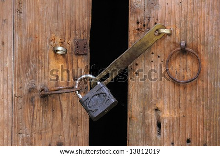 Padlock and chain on an wooden gate,shot in a small village,southeast of China. - stock photo