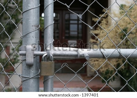 Padlock and gate detail on a security fence in front of a closed building.