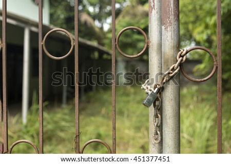 Padlock and old chain on metal fence - stock photo