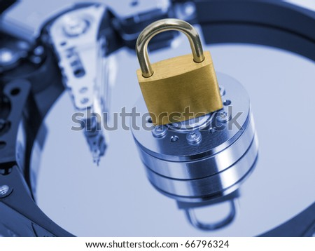 Padlock on blue toned  hard disk drive. Security concept. - stock photo