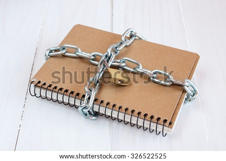 Padlock protects the notepad in a concept on protect the secret information - stock photo