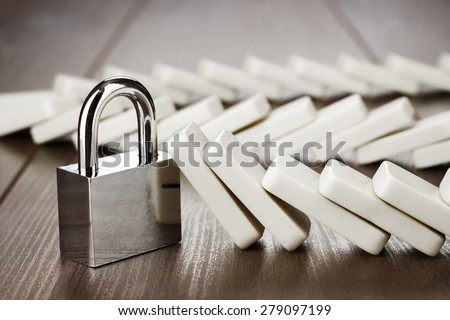 padlock standing still reliability concept on wooden table - stock photo