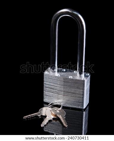 Padlock with keys isolated on black - stock photo