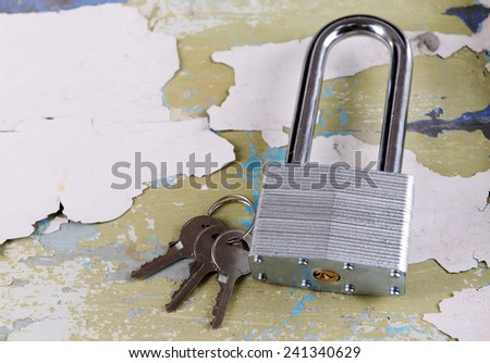 Padlock with keys on wooden background - stock photo