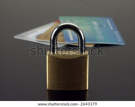 Padlock with out of focus credit cards in the background.