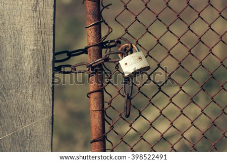 Padlock with shackle and locking mechanism one portable lock on unpainted rusty metal chain link fence gate outdoor closeup on blurred background  - stock photo