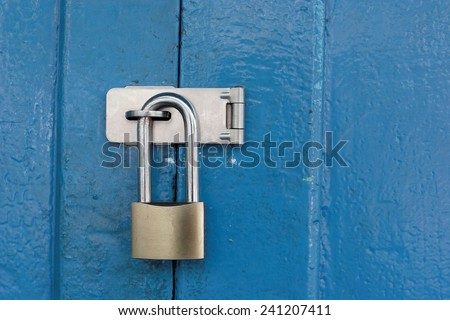 Padlocked on blue wooden door.