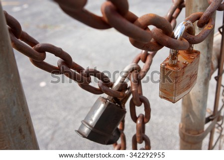 Padlocks And Rusted Chains Secure Gate At Industrial Site - stock photo