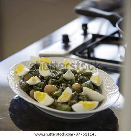 Padron Peppers Dish with hard-boiled eggs and baby potatoes - angle - stock photo