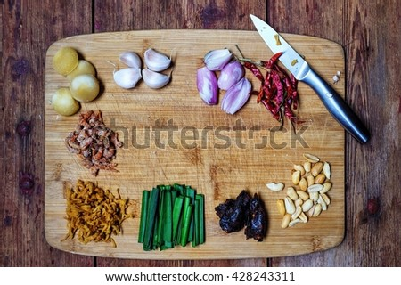 Padthai Ingredients ; from top left to right Palm sugar, garlic, shallots, dried chilies, dried shrimps, dried marinated white radish, garlic chive, tamarind and grilled peanut. Copy space at center - stock photo