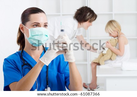 paediatrician with syringe in office, background is nurse and child patient