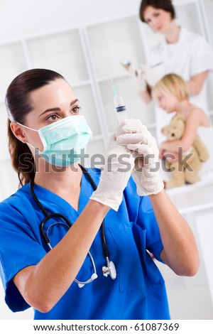paediatrician with syringe in office, background is nurse and child patient - stock photo