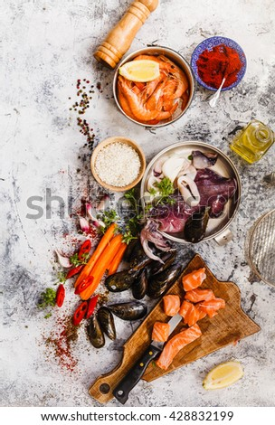 Paella a la margarita with shellfish including pink prawns, clams and mussels on saffron rice with peas for a delicious seafood meal, close up view. - stock photo