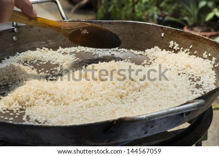 Paella is a typical spanish rice food. Frying the rice with the prawns juice. Preparing paella vintage set. - stock photo