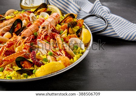Paella Valencia with fresh langoustines and assorted seafood and shellfish served on yellow saffron rice garnished with slices of fresh lemon, close up view - stock photo