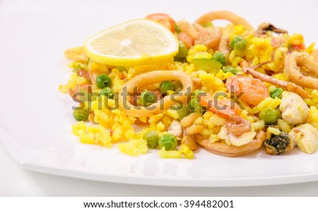 Paella with chicken and seafood on a white plate, close-up, side view - stock photo