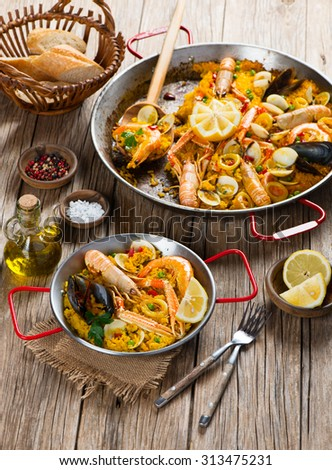 Paella with prawns, mussels and lemon, wooden background - stock photo