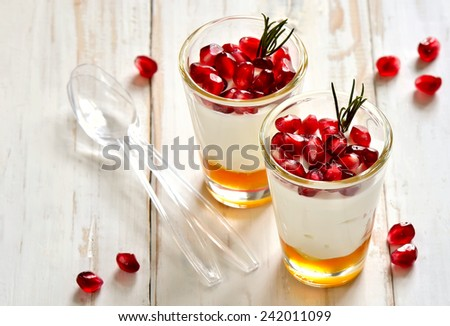 Pafait or yogurt with honey and juicy pomegranate seeds decorated with rosemary - stock photo