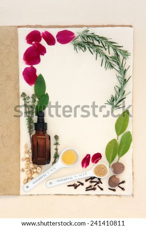Pagan love potion ingredients over natural hemp notebook and mottled cream paper background. - stock photo